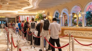 A long line of weary travelers wait to check in to the hotel at the Bellagio Las Vegas, a luxury hotel and casino on the Vegas Strip