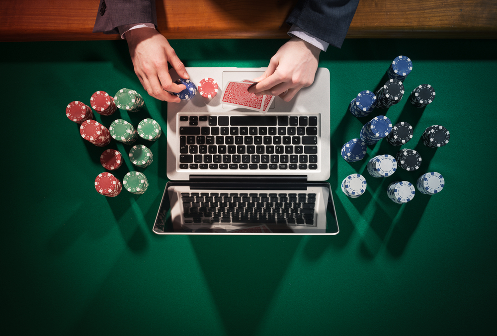 Man playing online poker with laptop on a green table with chips all around