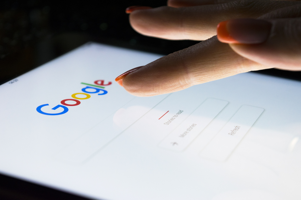 A woman's hand is touching screen on tablet computer iPad Pro at night for searching on Google search engine